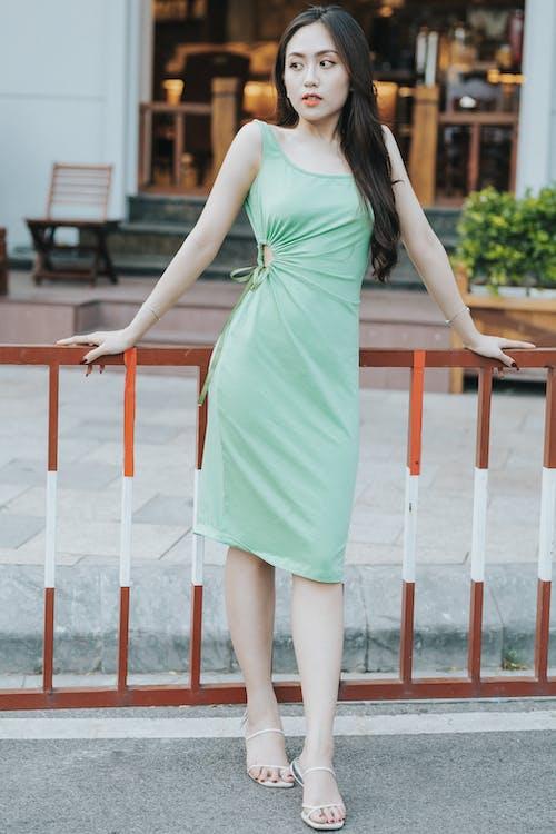Stylish dreamy Asian model in dress leaning on fence