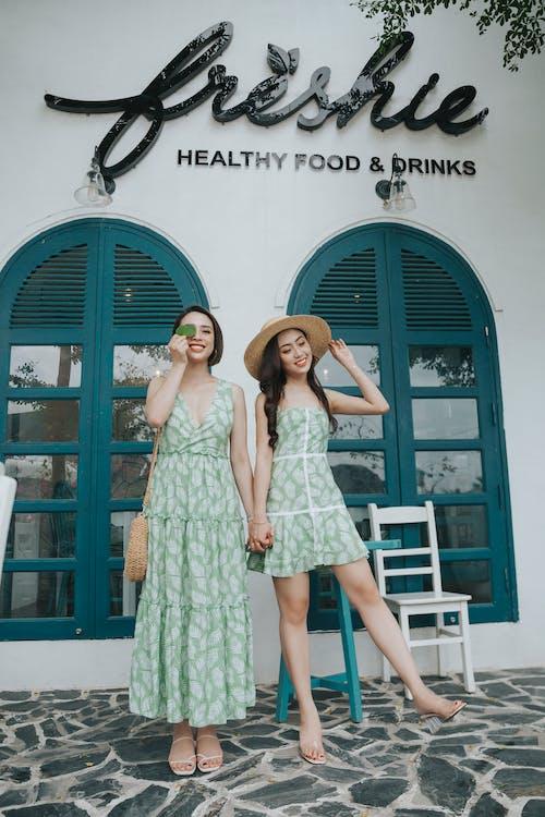 Stylish smiling Asian girlfriends in sundresses near restaurant