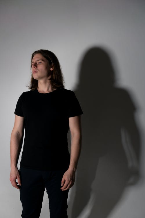 Young fit sad male in black outfit standing near wall with shadow and looking away
