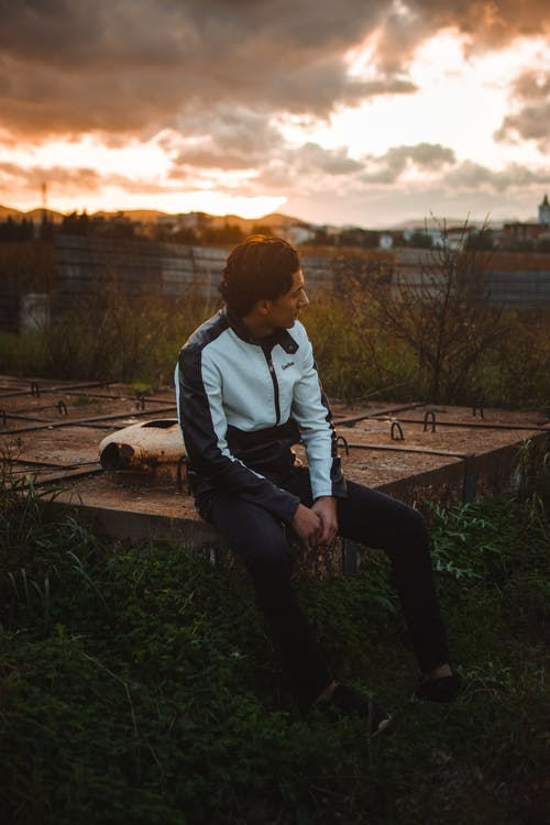 Man in Gray Hoodie Sitting on Brown Wooden Bench during Sunset