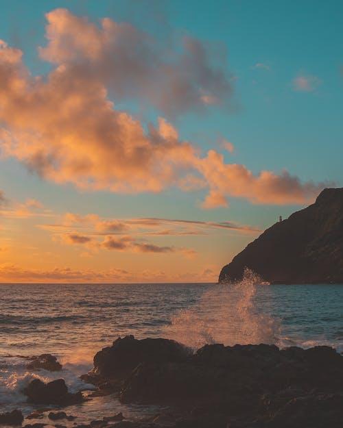 Ocean Waves Crashing on Black Rock Formation during Sunset