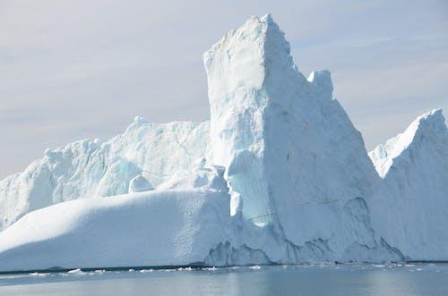 Shiny glacier near sea under cloudy sky