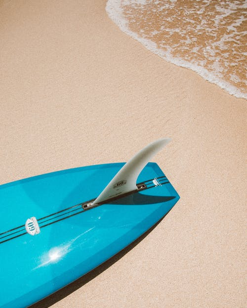 Blue Surfboard on White Sand Beach