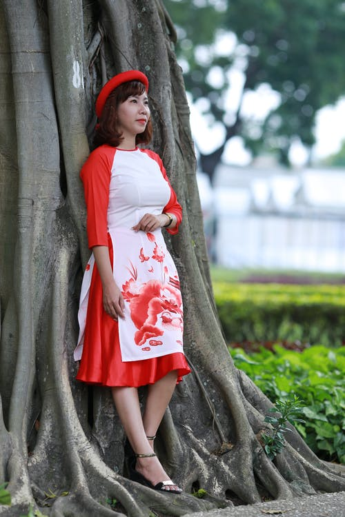 Thoughtful Asian woman leaning on tree in park