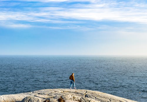 Anonymous person standing on stony cliff against blue endless sea
