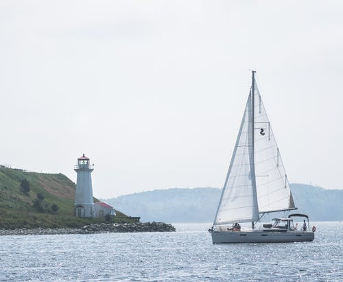 White yacht sailing near river coast with lighthouse