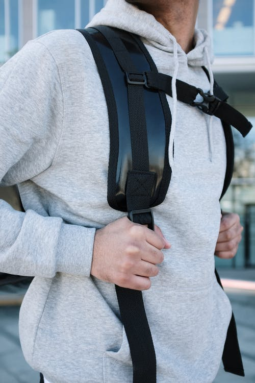 Person in Gray Sweater With Black Sling Bag