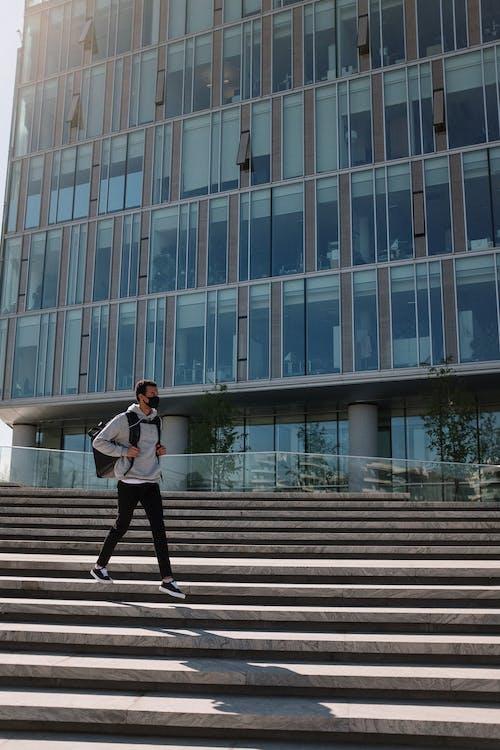 Woman in White Long Sleeve Shirt and Black Pants Walking on Pedestrian Lane