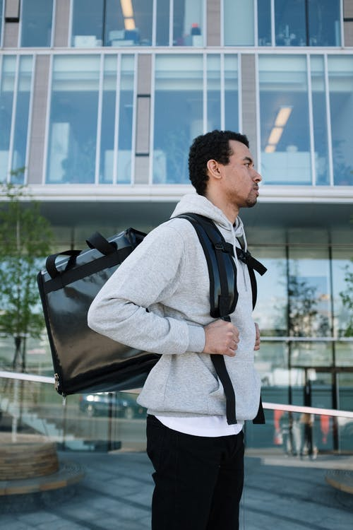 Man in Gray Vest and White Long Sleeve Shirt Holding Black Leather Sling Bag