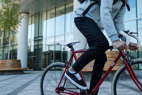 Person in Gray Jacket Riding Red Bicycle