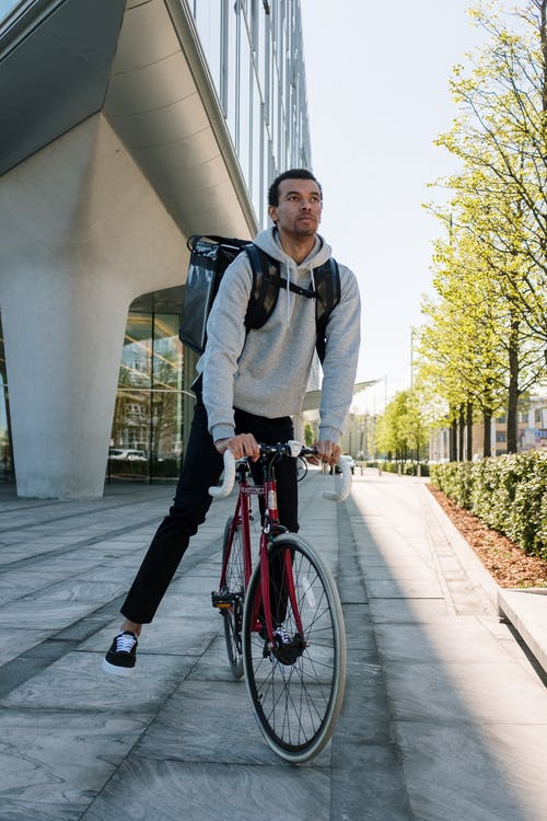 Man in Black Jacket and Black Pants Riding Red Bicycle