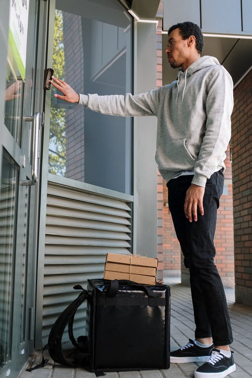 Man in Gray Sweater and Black Pants Standing Beside Glass Window
