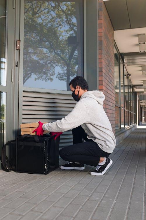 Man in Gray Hoodie and Black Pants Sitting on Black Luggage Bag