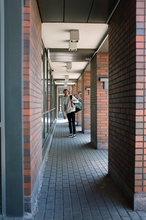 Man in White Dress Shirt Walking on Hallway