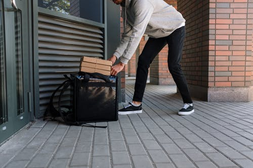 Man in White Dress Shirt and Blue Denim Jeans Holding Black Luggage Bag