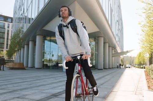 Man in Gray Sweater Riding Red Bicycle