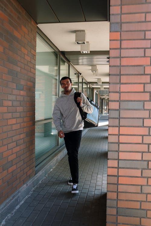 Man in Gray Jacket Standing Beside Brown Brick Wall