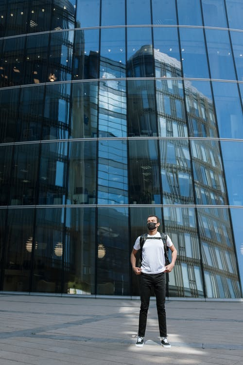 Man in White Shirt Standing in Front of Glass Building