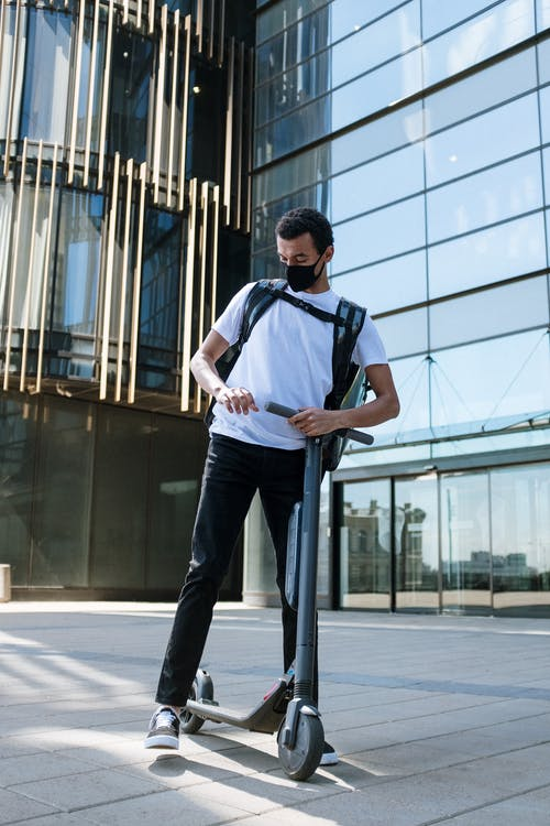 Man in Blue Crew Neck T-shirt and Black Pants Standing Near Glass Building