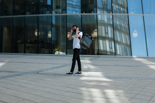 Woman in White Jacket and Black Pants Standing Near Glass Building