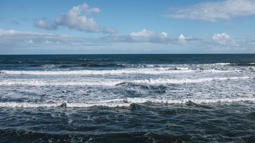 Picturesque view of foamy sea waves rolling towards coast beneath clear sky on sunny day