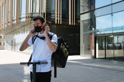 Man in White T-shirt and Black Pants Holding Black Camera