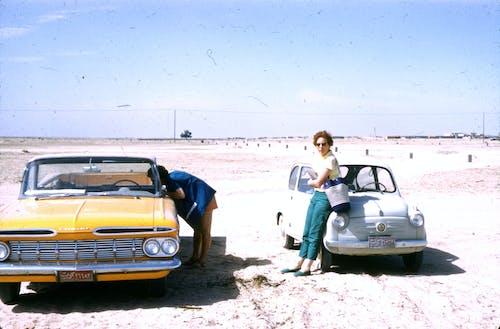 Woman in White Shirt Standing Beside Yellow Car