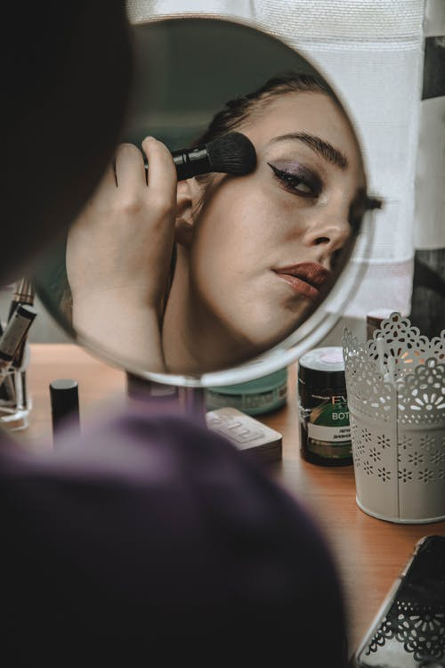 Crop woman looking in mirror and applying blush on face