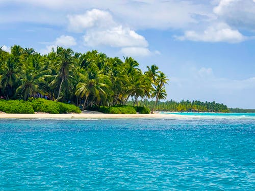 Green tropical island washed by azure seawater