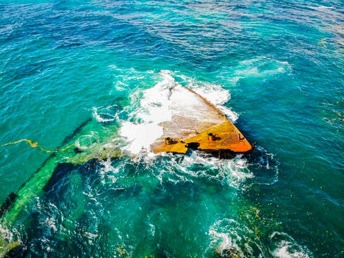 From above rusted grunge fragments of crashed boat lying in shallow sea and washed by clean green water