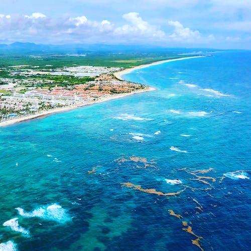 Modern settlement on tropical coastline near blue sea