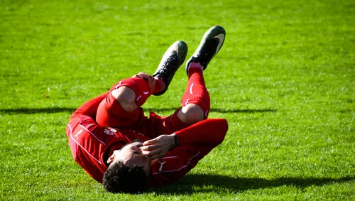 Soccer Player Lying on Ground While Holding His Leg