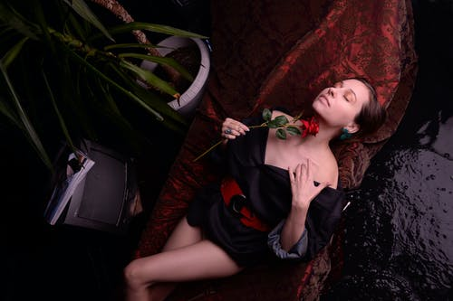 Sensual woman with rose lying in red coverlet near brook