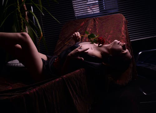 Alluring woman with rose lying provocatively on chair in darkness