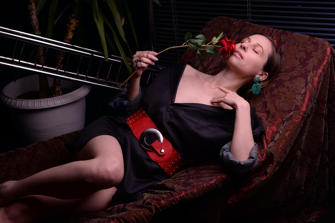 Gorgeous woman lying on chair gracefully and smelling rose
