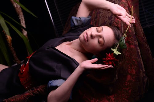 Relaxed alluring woman with rose lying on chair