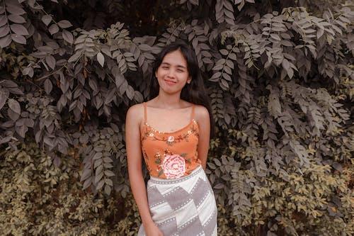 Positive Asian woman near green fence