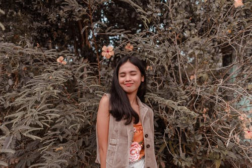 Happy Asian woman standing with eyes closed against lush tree