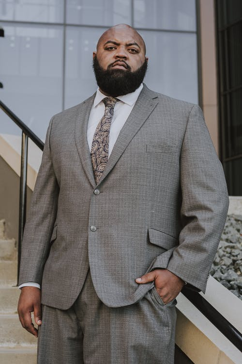 Low angle of serious bearded adult black male manager in formal suit and tie standing on staircase near modern building with hand in pocket and looking at camera