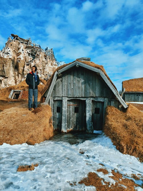 Man admiring nature standing near shack in snowy countryside in highland