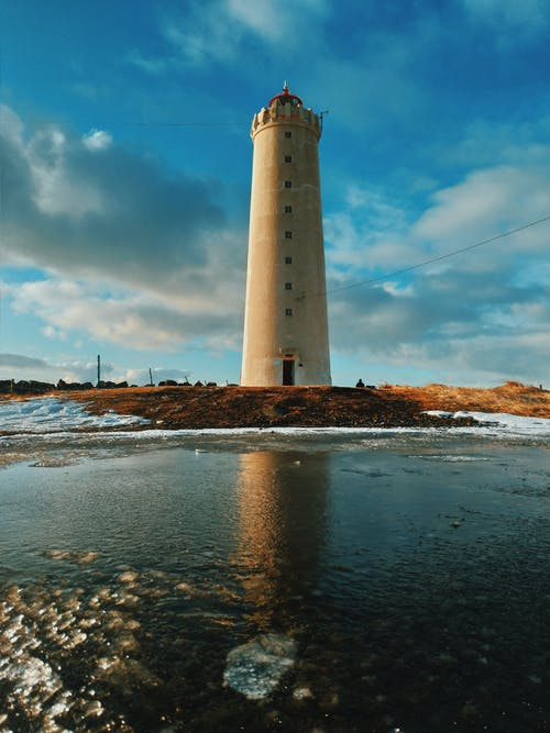 Low angle of aged Grotta Lighthouse locate don grassy hill near frozen sea against cloudy blue sky in Seltjarnarnes town