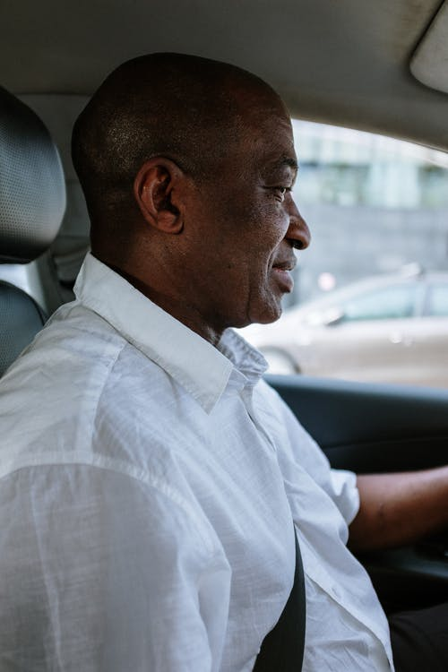 Man in White Button Up Shirt Driving Car
