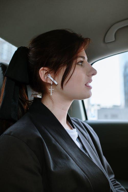 Woman in Black Shirt Wearing White Earbuds