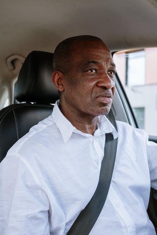Man in White Polo Shirt Sitting on Car Seat