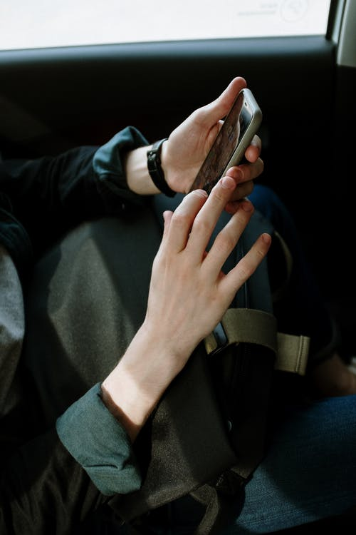Person in Black Jacket Holding Smartphone