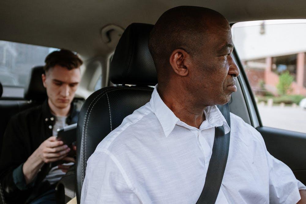 Man in white dress shirt sitting on the car seat.   Photo: Pexels