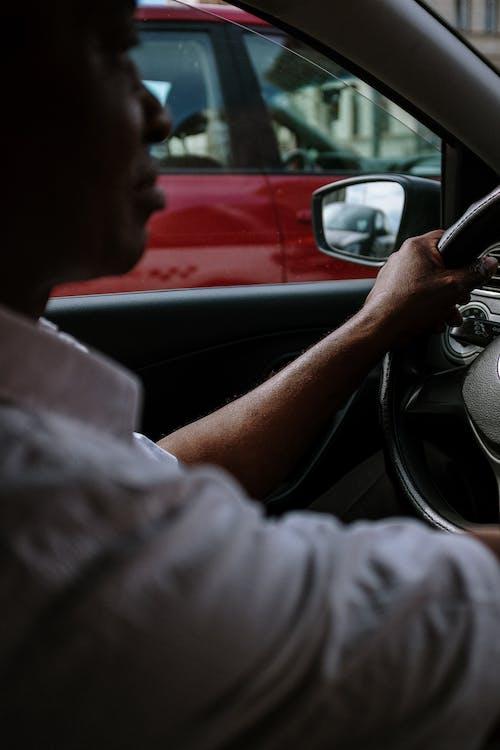 Man in Gray Long Sleeve Shirt Driving Car