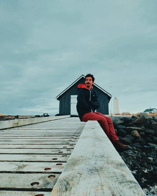 Woman in Red Long Sleeve Shirt and Red Pants Standing on Gray Wooden Dock