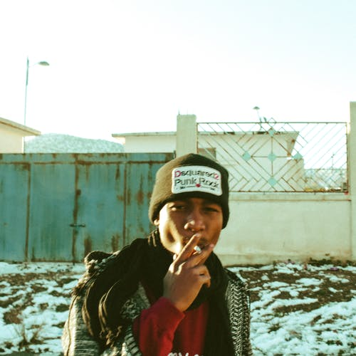 Young black guy smoking cigarette in wintertime