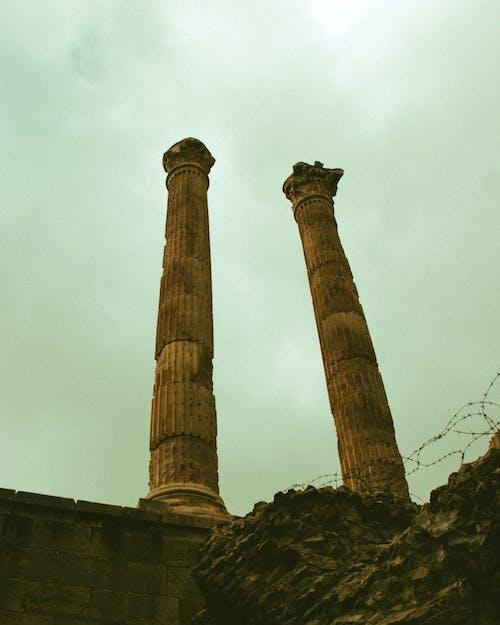 Ancient antique yellow columns above big stone
